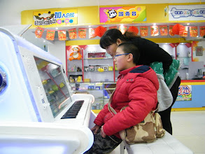 Photo: woz trying e-piano toy on mall when his uncle's family invited us to go shopping. here his aunt watching in background.