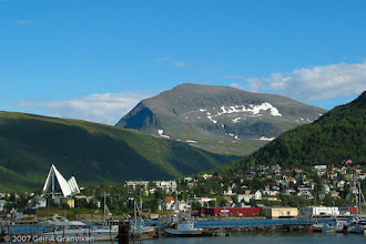 """Photo: View from Tromsø, with Tromsdalen church, also known as Ishavskatedralen (directly translated as """"the polar ocean cathedral""""), and the mountain Tromsdalstinden."""