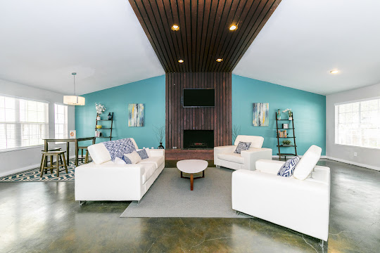 Clubhouse interior with a dark brown wood slat fireplace feature, mounted TV, two oversize white chairs, and white couch