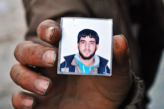 Photo: A Free Syrian Army rebel fighter holds up a portrait of one of his friends killed in battle. Aleppo, SYRIA - 11/4/2013. Credit: Ali Mustafa/SIPA Press