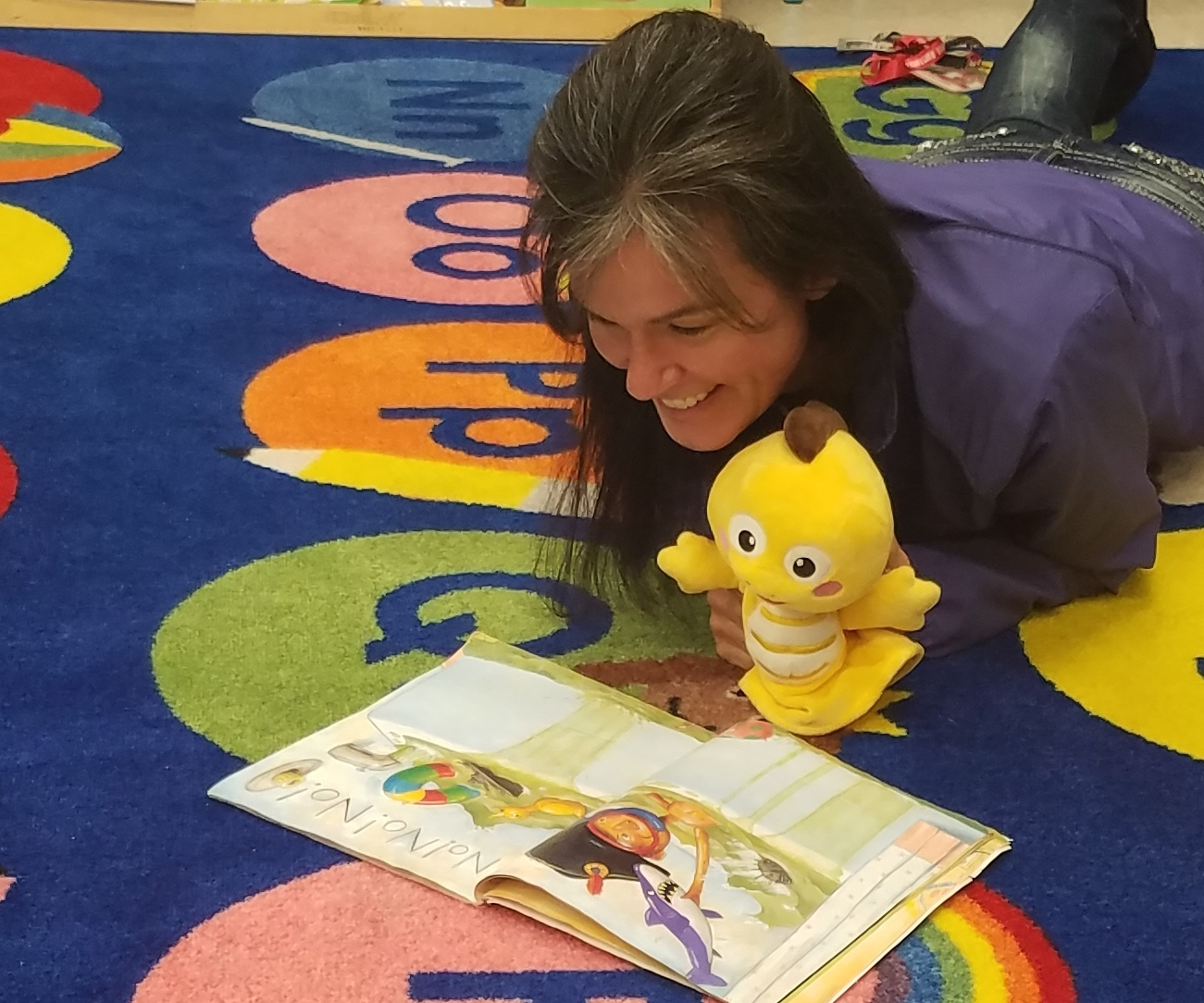 Teacher Nichole reading with Dino in her classroom