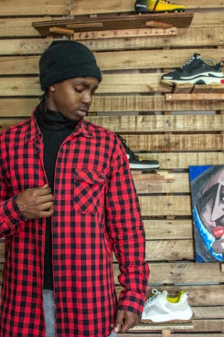 A photo of Kevin. He wears a cool red and black checked shirt, posing for the camera as he looks downward. He stands in front of a shoe display with sneakers on wooden shelves.