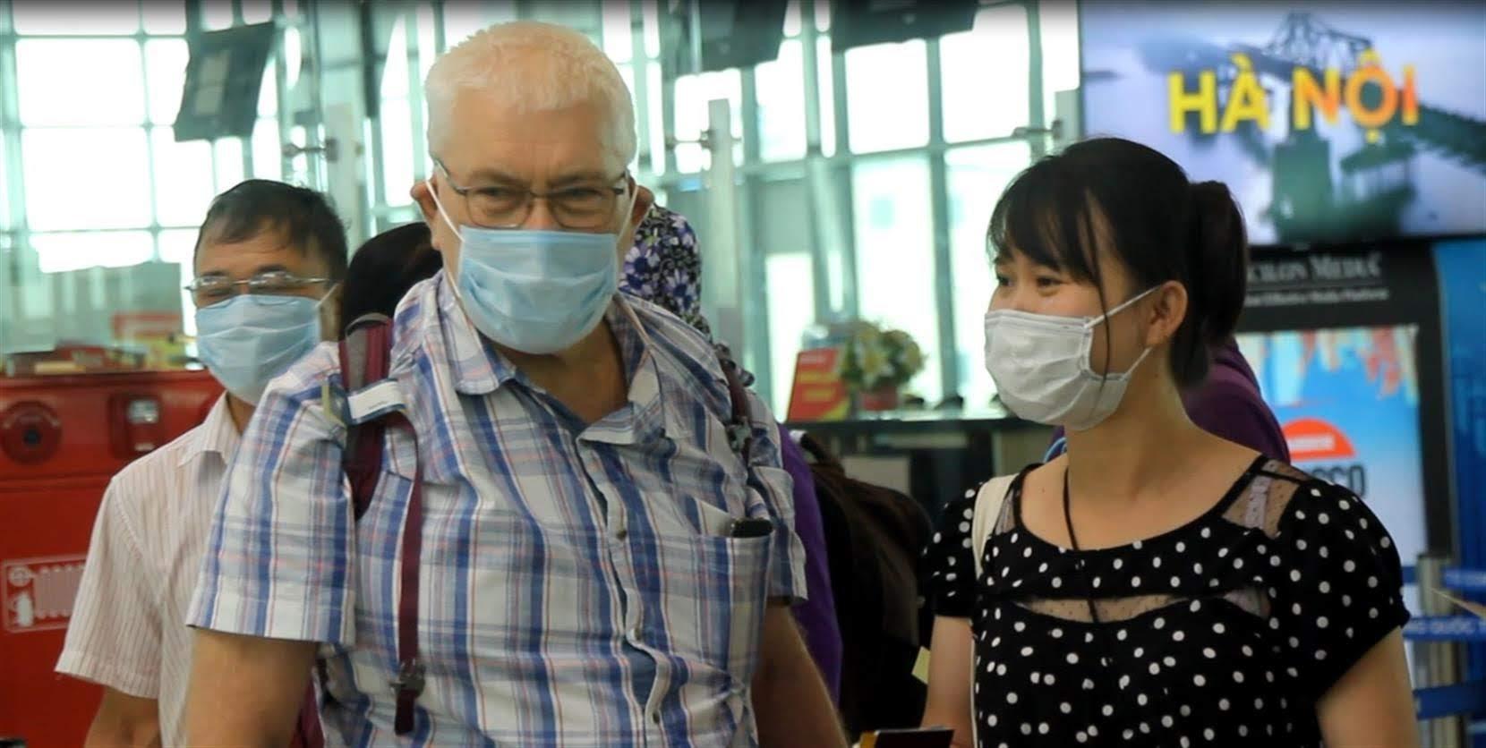 Một hành khách nước ngoài đeo khẩu trang trong khi làm thủ tục tại Sân bay quốc tế Vinh.