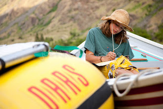 Photo: Young woman writing in journal while rafting Hell's Canyon of the Snake River, ID / OR. Hell's Canyon is the deepest canyon in North America.