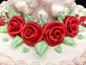 Photo: Red frosting roses dusted w/edible glitter & green foliage.