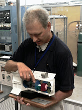 Photo: NASA staff explains a model version of the Advanced Stirling Convertor