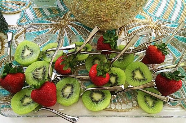 Peel the kiwi and then cut in thick slices.  Slowly push the sticks...