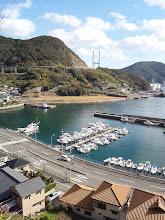Photo: 高台から撮ったうちの港の写真をバックに。 今年も一年、大変、大変お世話になりました。 いたらぬところばかりでご迷惑も多々お掛けいたしました。来年はその迷惑を減らしつつ、更に楽しい、楽しいひと時を過ごせる時間を作っていきたいと思っております! 本当にありがとうございました!来年もよろしくお願い致します。 恵丸 船長 入江孝和