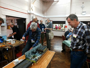 Photo: 004 Alan Hamer negotiates the assault course in order to get behind his own layout, whilst Ed Florey from the SWOONS Group tries to find his entrance fee as fellow SWOONS member Geoff Bowyer talks to Lee Bryant from the Wessex NGM and Brian Ellsmore (one of the 009 Society Sales team) looks cool. In the foreground is David Collins who is otherwise known as Clayliner to members of NGRM-Online and the 009 Society forum .