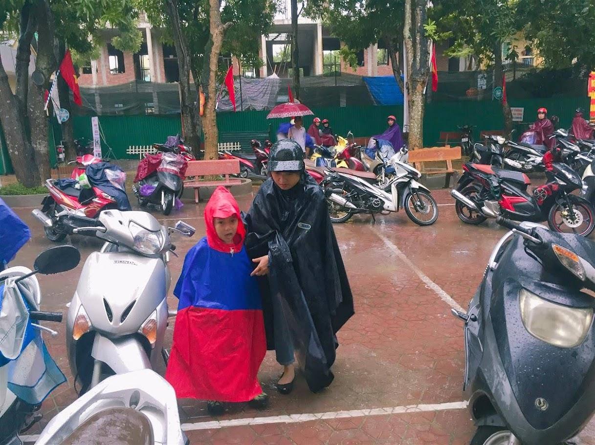 Do trời mưa to liên tục trong nhiều ngày, phụ huynh phải đội mưa, che chắn cho các em học sinh bằng áo mưa, ô…để đưa các em kịp dự lễ khai giảng năm học mới