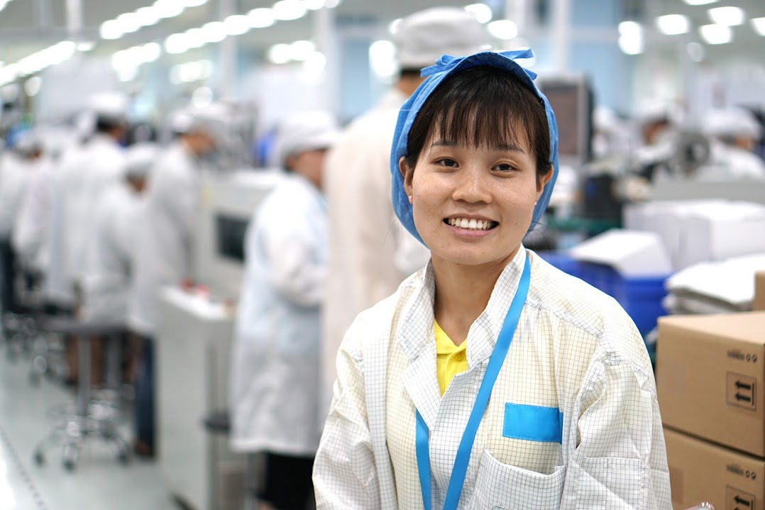 A person smiling at the camera and wearing a factory uniform.