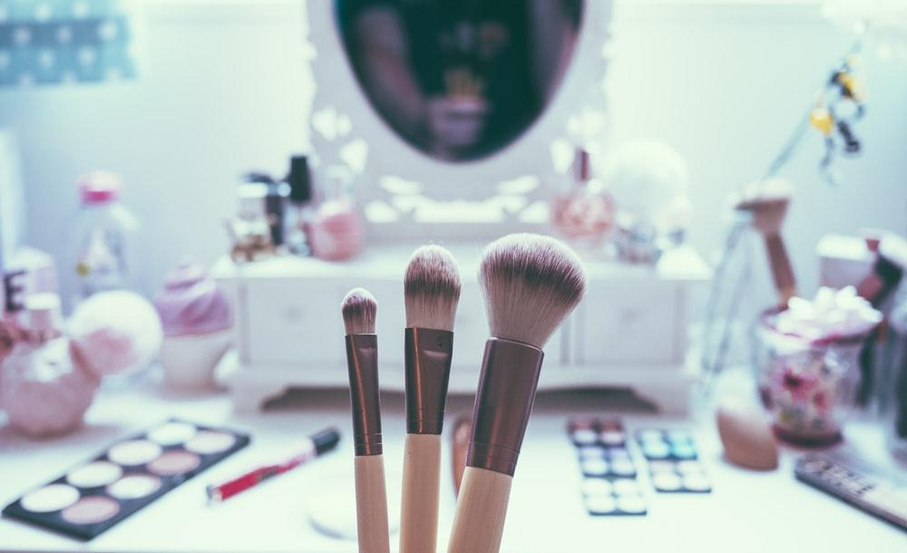 macro shot of three brown makeup brushes