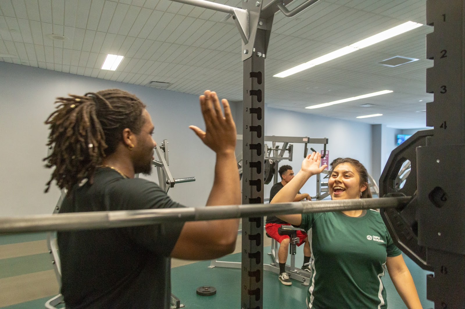 A member going in for a high five with Arellano Rodriguez after a personal training session