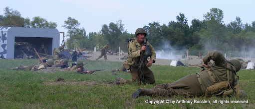 Photo: GIs advance on beach past German bunker.