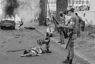 Photo: 06 Jan 1969, Saigon, Vietnam --- A member of the military police stands over South Vietnamese Minister of Education Dr. Le Minh Tri, who lies bloodied in the street following a Vietcong bombing of his car in Saigon. Le Minh Tri and his bodyguard sustained multiple wounds after a Vietcong soldier threw a hand grenade into the car, killing the driver. --- Image by © Bettmann/CORBIS
