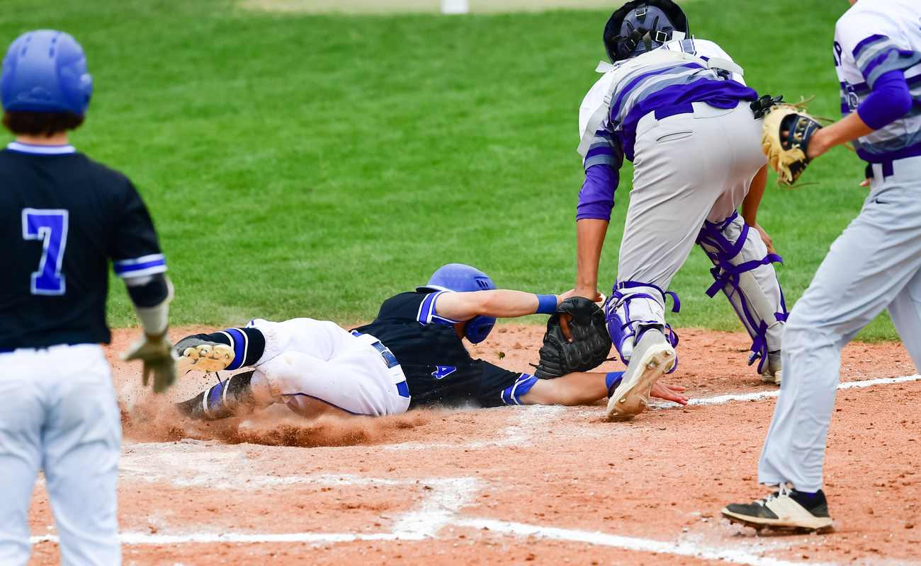 Baseball player sliding on the diamond with opposing players on the field
