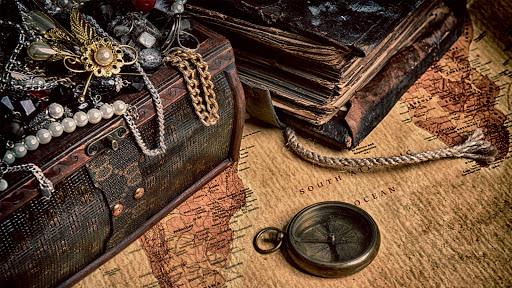 Libros y joyas de un tesoro sobre un mapa antiguo