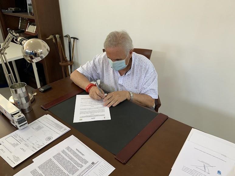 Firmando un convenio con el ayuntamiento.
