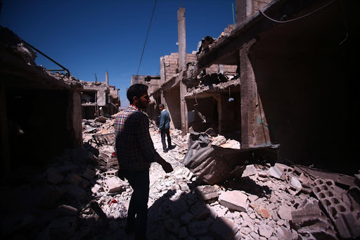 People inspect damaged buildings that were targeted by airstrikes in Deir al-Asafir district, southeast of Damascus, Syria. Picture Credit: EPA