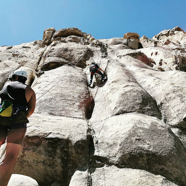 Person climbing up a mountain face with another person belaying them on the ground.