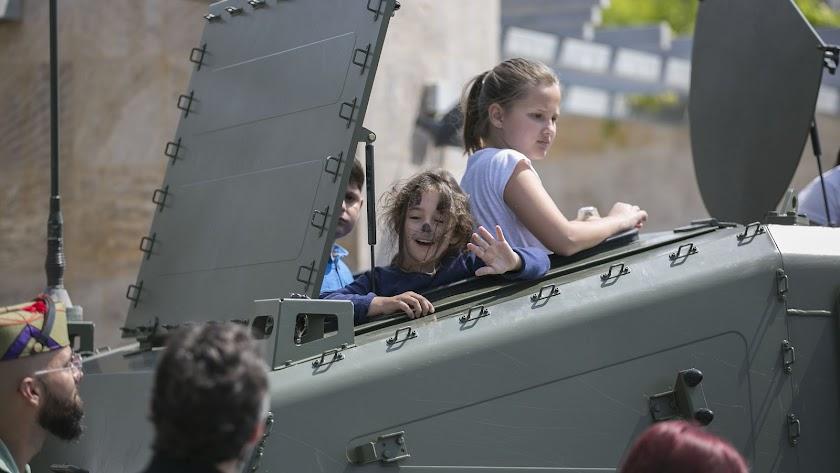 Alegría en la mirada de una niña subida a uno de los camiones de la Legión, un vehículo de 'alta movilidad táctica'.