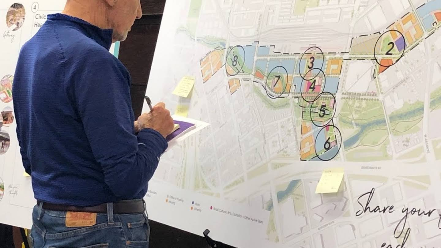 A man standing in front of a map of San Jose taking notes.