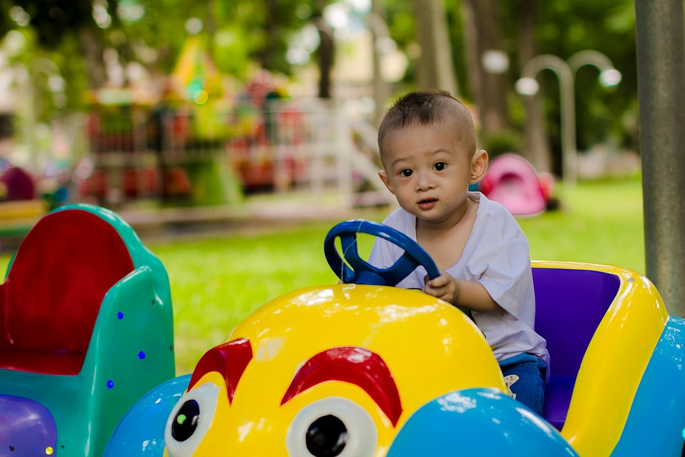 A baby in a play car! Very cute image if I may add. Found from https://pixabay.com/photos/child-play-park-kid-ku-shin-1679581/
