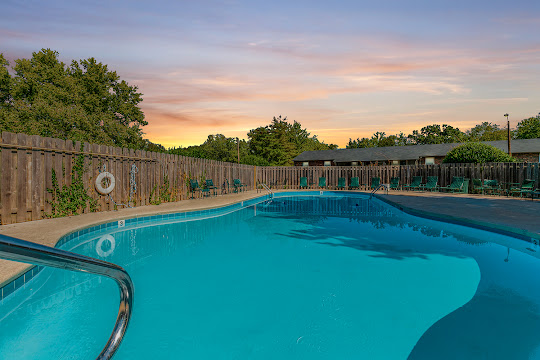 Apartment swimming pool surrounded by patio furniture at dusk