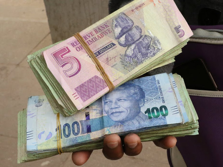 An illegal money changer holds bond notes outside a bank in Zimbabwe's capital Harare.