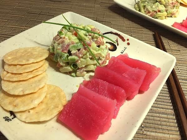 Slices Of Tuna On A Plate With Rice Crackers And A Slaw Garnished With Chives.