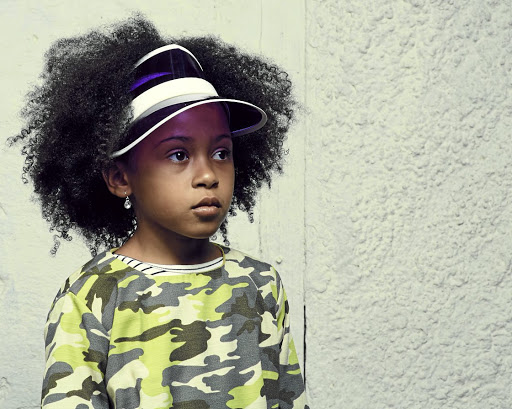 When styling your child's afro, gather a small amount of hair at a time and lightly comb out with a wide-toothed comb.