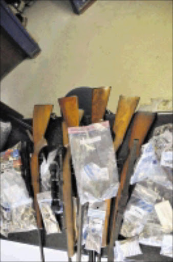 CACHE: Firearms and ammunition found at the house of a shebeen queen who shot her customers in Crystal Park, Benoni, at the weekend. PHOTO: VATHISWA RUSELO.  11/10/2009. © Sowetan.