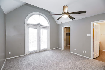 Bedroom with light carpet, light walls, ceiling fan, and patio door