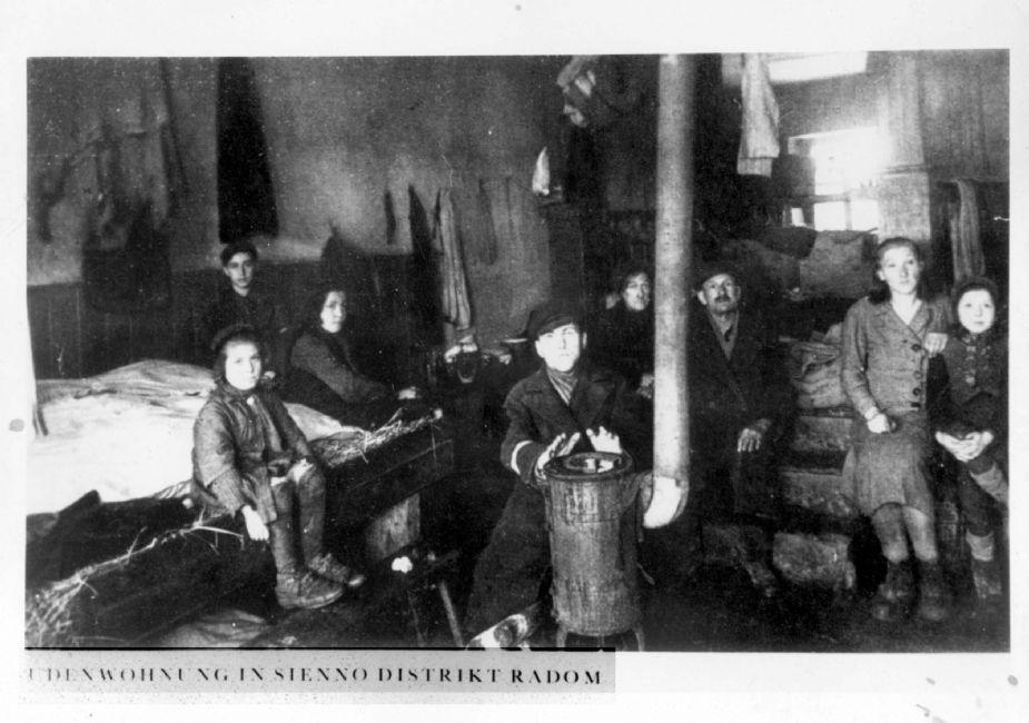 Poland ,Radom, יהודים מתחממים סביב אח בחדר בגטו. ארכיון יד ושם, 1605/1824