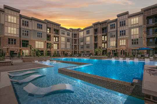 Artesia Big Creek resort-style pool with apartment building in the background at dusk