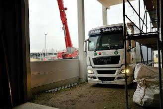 Photo: 09-11-2012 © ervanofoto De afwerking van de muur verloopt vlot. De tweede laag is al aangebracht. De vrachtwagen met de ramen staat klaar om gelost te worden.