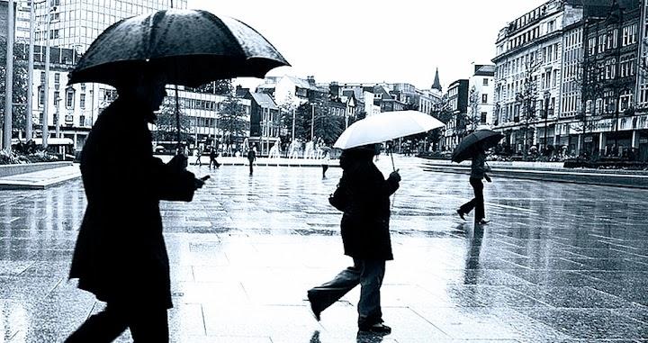 Dunkle Gestalten mit Regenschirmen.