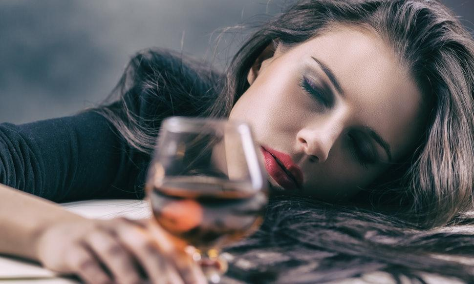 glass of alcohol and sleeping woman