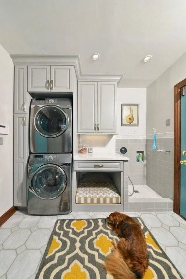 stacked washer dryer with grey cabinets and small dog bed next to a walk in dog bath
