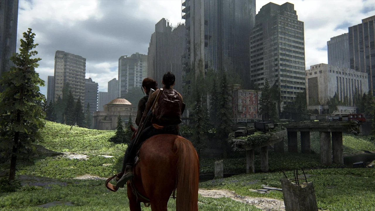 Ellie and Dina ride horseback into a open world section of post-apocalyptic Seattle