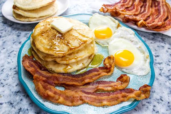 Slices Of Crisp Bacon With Pancakes And Eggs.