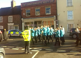 Photo: The bands follow the clergy, the Police keeping North St clear for the short service at the Memorial hospital.
