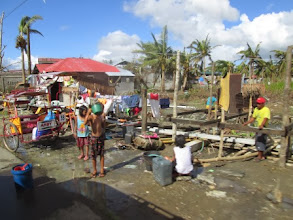 Photo: Residents line up for the only water source in the village since typhoon Haiyan destroyed the other water sources