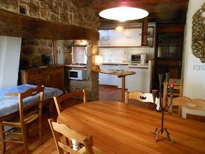 Photo: Au 1er plan : table en merisier pour 7 à 8 personnes. A l'arrière : cuisine. A gauche : table de desserte.