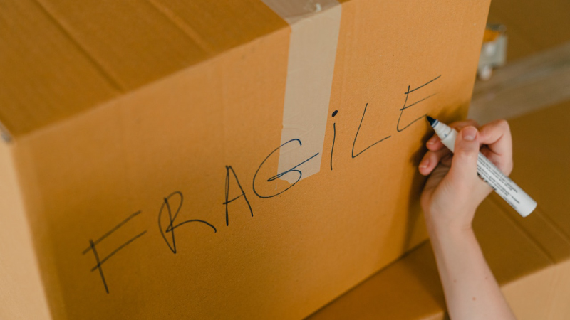 Writing fragile on a box going into storage