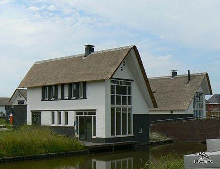 Dwa domki nad kanałem wodnym z dużymi oknami i spadzistym dachem z trzciny
