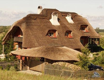 Czerwony dwupiętrowy dom z olbrzymim dachem trzcinowym i białymi kominami