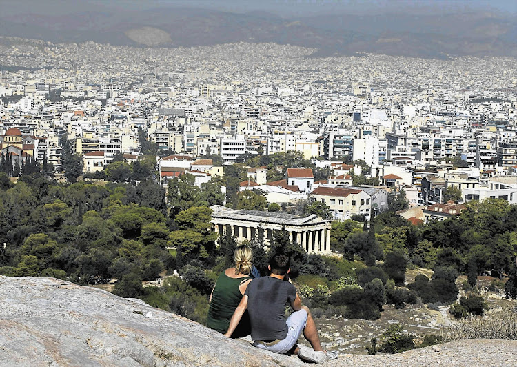 Tourists on a hill in Athens view the archaeological site of the Acropolis in Greece. File photo.