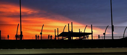 Photo: Fans standing behind a catch fence at race track as orange Sun sets behind them.