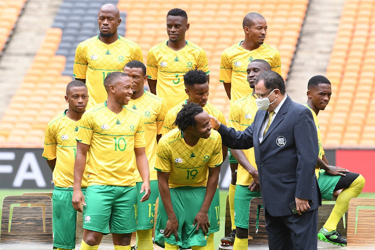 Safa president Danny Jordaan greets Percy Tau and the Bafana Bafana team during their team photo session at FNB Stadium in Johannesburg on March 24 2021.